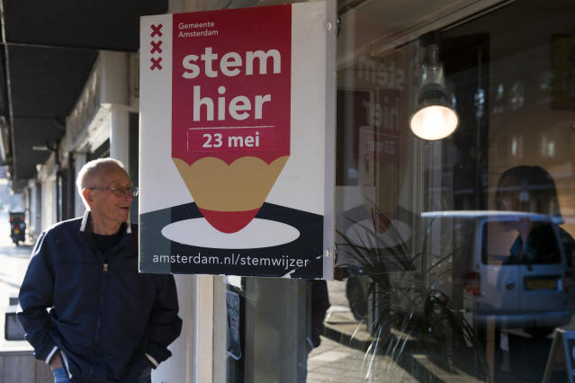 A man asks an election official for the opening time of the polling station before casting his ballot for the European elections in Amsterdam, Netherlands, Thursday, May 23, 2019. Dutch polls have opened in elections for the European Parliament, starting four days of voting across the 28-nation bloc that pits supporters of deeper integration against populist Euroskeptics who want more power for their national governments. (AP Photo/Peter Dejong)