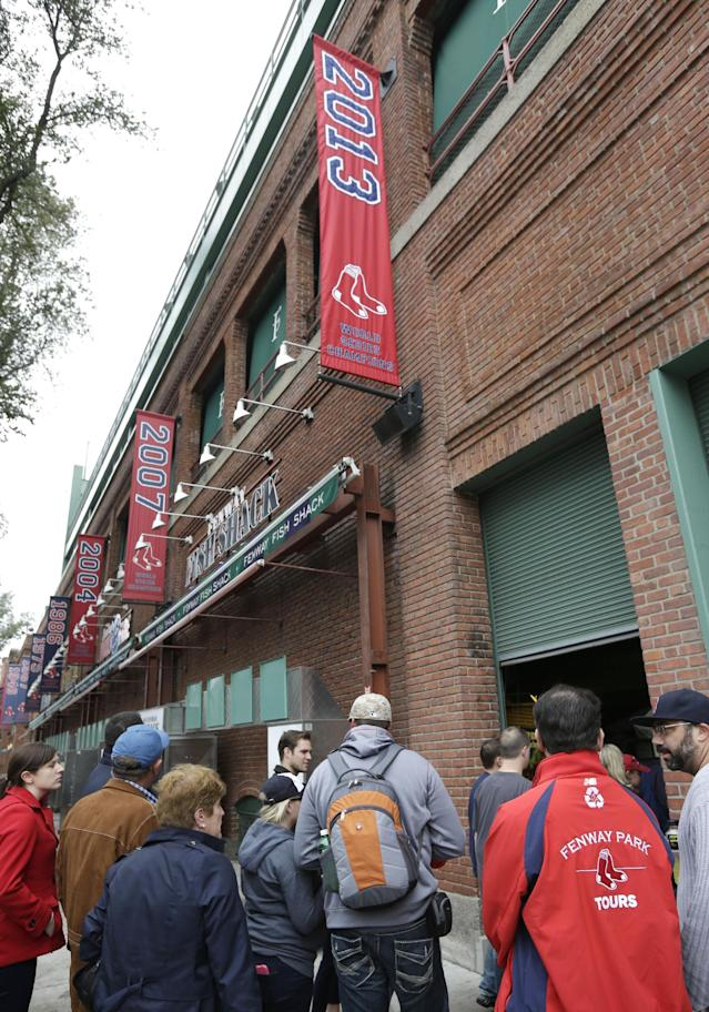 A tour group enters Fenway Park in Boston, Thursday, Oct. 31, 2013, under a 2013 baseball World Series champions banner, top. The Boston Red Sox defeated the St. Louis Cardinals 6-1 in Game 6 of baseball's World Series on Wednesday to win the series. (AP Photo/Steven Senne)