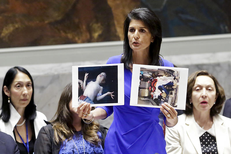 US Ambassador to the UN Nikki Haley holds up pictures showing alleged victims of a chemical gas attack in Syria's rebel-held Idlib province: AP