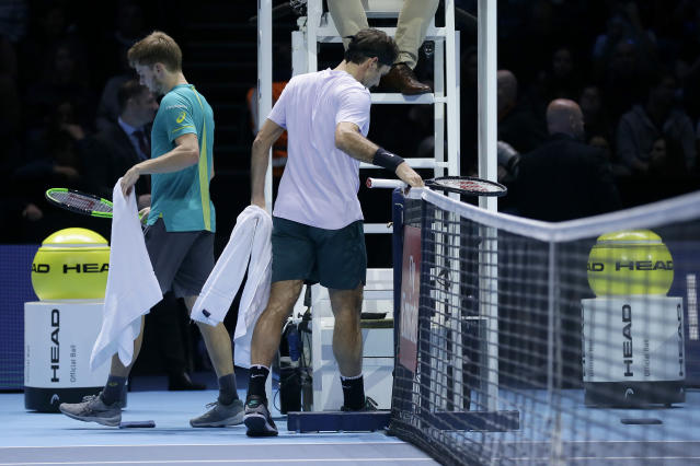 David Goffin of Belgium, left, and Roger Federer of Switzerland change ends during their ATP World Tour Finals semifinal tennis match at the O2 Arena in London, Saturday Nov. 18, 2017. (AP Photo/Tim Ireland)