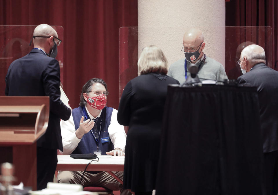 FILE - In this Nov. 20, 2020, file photo, Dane County Clerk Scott McDonell, seated, converses with election workers and legal representatives from the Joe Biden and Donald Trump presidential campaigns as a recount of the 2020 presidential election begins at the Monona Terrace convention center in Madison, Wis. President Trump filed a lawsuit Tuesday, Dec. 1, 2020, in Wisconsin, seeking to disqualify hundreds of thousands of ballots in a longshot attempt to overturn Democrat Joe Biden's win in the battleground state he lost by nearly 20,700 votes. (John Hart/Wisconsin State Journal via AP, File)