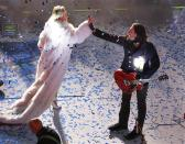 Miley Cyrus (L) congratulates a member of her band after performing for revelers in Times Square during New Year's Eve celebrations in New York December 31, 2013. REUTERS/Gary Hershorn