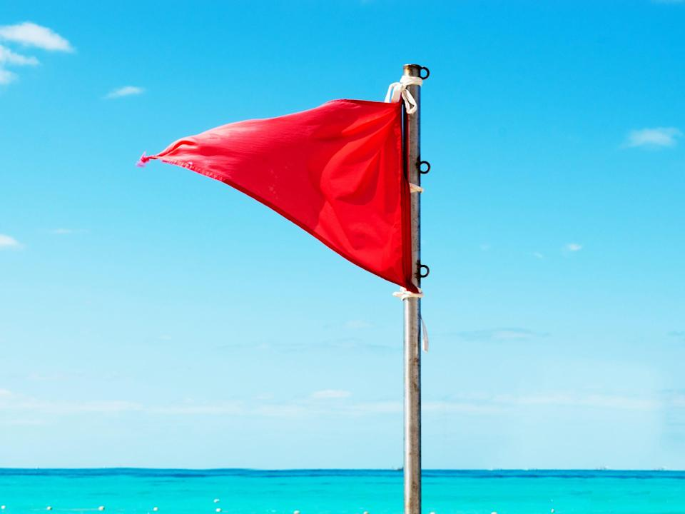 a triangle shaped red flag on a pole with a turquoise sky and sea background