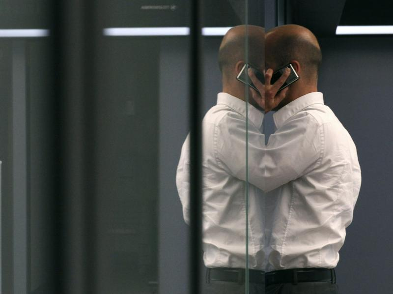 A bourse trader uses a cell phone during a trading session on the trading floor at Frankfurt's stock exchange