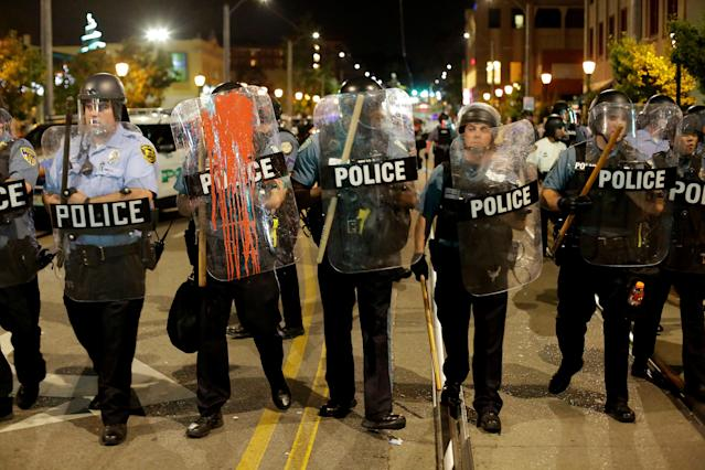 <p>Police officers watch as people march the day after the not guilty verdict in the murder trial of Jason Stockley, a former St. Louis police officer, charged with the 2011 shooting of Anthony Lamar Smith, who was black, in St. Louis, Mo., Sept. 16, 2017. (Photo: Joshua Lott/Reuters) </p>