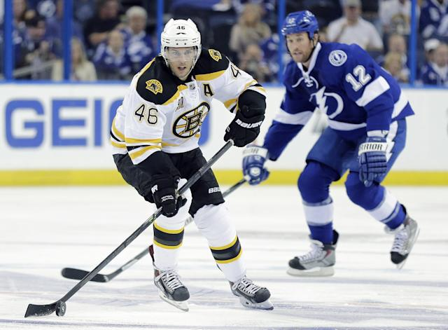 Boston Bruins center David Krejci (46), of the Czech Republic, carries the puck ahead of Tampa Bay Lightning left wing Ryan Malone (12) during the first period of an NHL hockey game Saturday, Oct. 19, 2013, in Tampa, Fla. (AP Photo/Chris O'Meara)