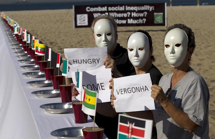 """People protest beside a table set with empty plates and national flags as they hold signs that read from right to left in Portuguese; """"Shame, hunger"""" at the Copacabana beach during the United Nations Conference on Sustainable Development, or Rio+20, in Rio de Janeiro, Brazil, Tuesday, June 19, 2012. The Earth summit runs through June 22. (AP Photo/Silvia Izquierdo)"""