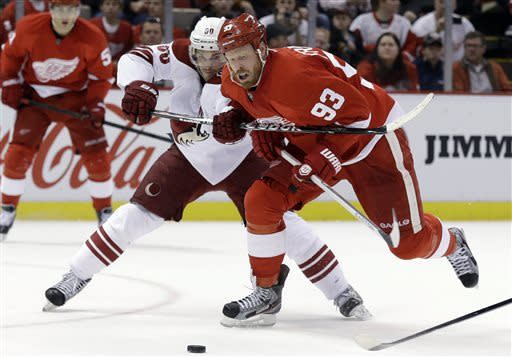Phoenix Coyotes center Antoine Vermette, left, tries to hold back Detroit Red Wings wing Johan Franzen (93), of Sweden, in the second period of an NHL hockey game in Detroit, Monday April 22, 2013. (AP Photo/Paul Sancya)