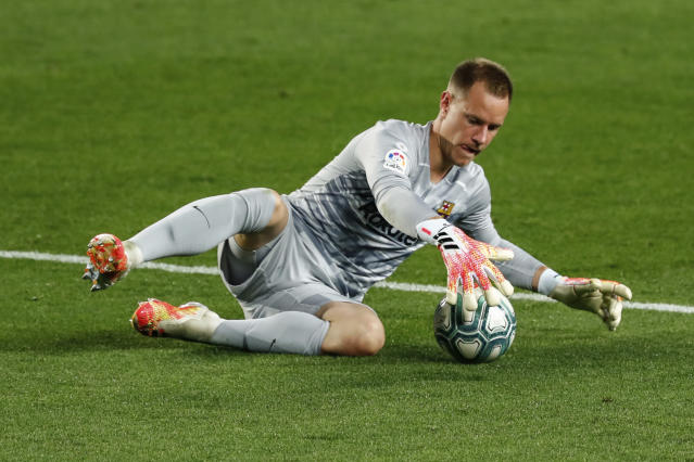 Barcelona's goalkeeper Marc-Andre ter Stegen stops the ball during the Spanish La Liga soccer match between FC Barcelona and Atletico Madrid at the Camp Nou stadium in Barcelona, Spain, Tuesday, June 30, 2020. (AP Photo/Joan Monfort)