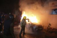 A security officer tries to put off a fire after after violence erupted Friday during a protest against the Citizenship Amendment Act in New Delhi, India, Friday, Dec. 20, 2019. Police banned public gatherings in parts of the Indian capital and other cities for a third day Friday and cut internet services to try to stop growing protests against a new citizenship law that have left 11 people dead and more than 4,000 others detained. (AP Photo)