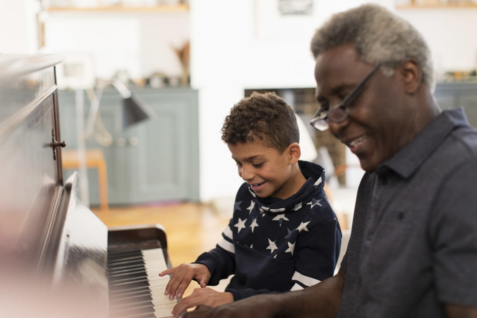 Child playing piano with his grandfather.