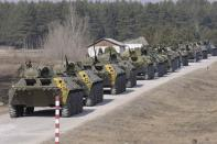 Ukrainian soldiers ride on military armoured personnel carriers as they take part in a military exercise near Kharkiv March 14, 2014. U.S. President Barack Obama said on Friday he still hopes for a diplomatic solution to the Ukraine crisis heading into a pivotal weekend. REUTERS/Stringer
