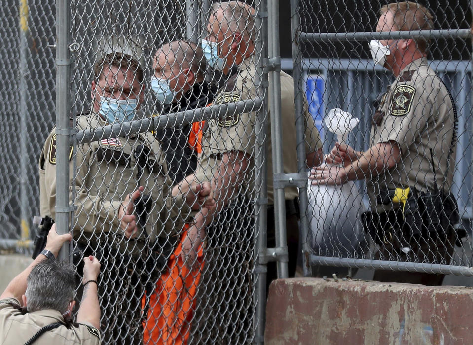 A law enforcement officer goes down while opening a gate for former Minneapolis police officer Derek Chauvin as fellow officers escorted Chauvin from the rear of the the Hennepin County Family Justice Center after a hearing for the four former police officers charged in the death of George Floyd, Friday, Sept. 11, 2020, in Minneapolis. The former officers appeared in court for a hearing on the prosecution's request to hold a joint trial and other issues. Floyd, who was Black, died May 25 after Chauvin pressed his knee against his neck during an arrest. (David Joles/Star Tribune via AP)