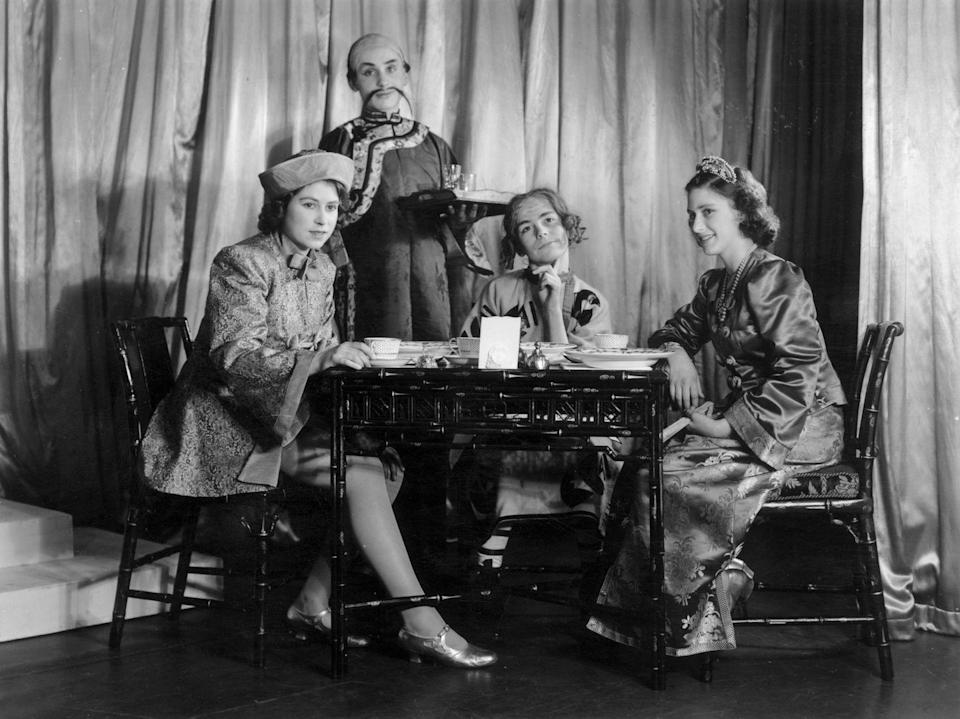 "<p>Princess Margaret and then-Princess Elizabeth share some tea onstage during a production of ""Aladdin""—one of <a href=""https://www.townandcountrymag.com/society/tradition/a25311105/queen-elizabeth-princess-margaret-wwii-christmas-play-photos/"" rel=""nofollow noopener"" target=""_blank"" data-ylk=""slk:their WWII-era Christmas pantomimes"" class=""link rapid-noclick-resp"">their WWII-era Christmas pantomimes</a>.<br></p>"