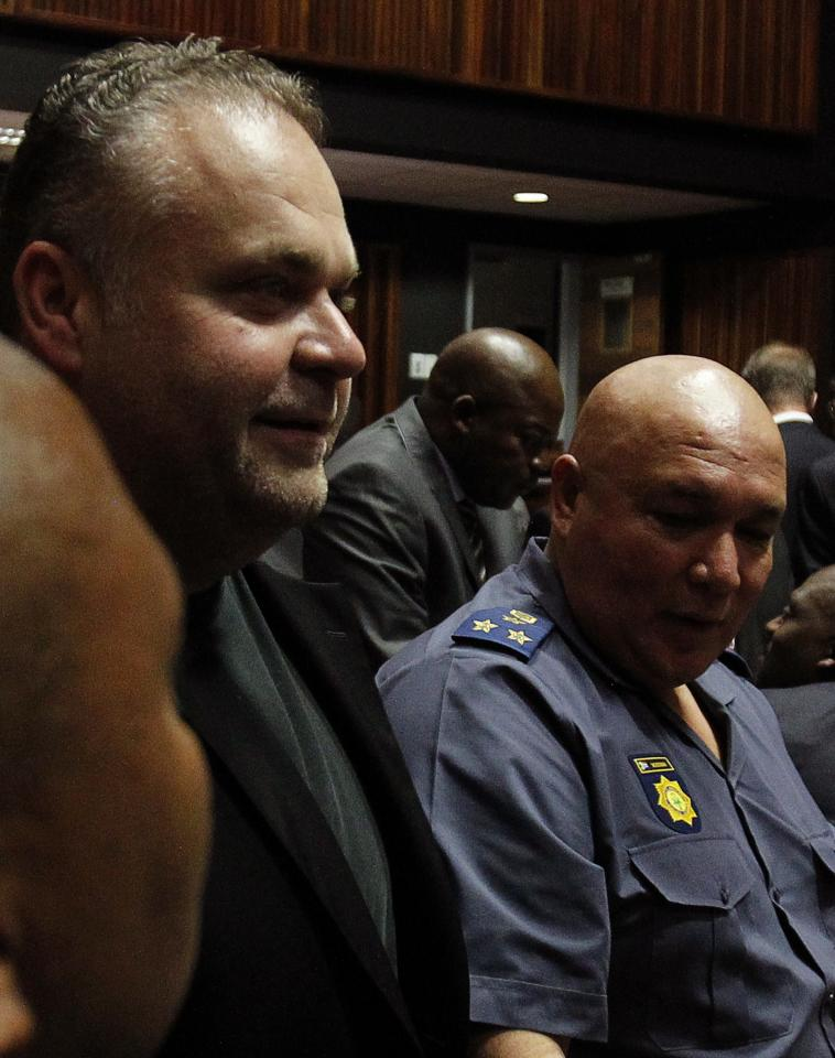 Radovan Krejcir (L), a Czech fugitive and businessman looks on during his court appearance on charges of kidnapping and attempted murder at the Palm Ridge court, east of Johannesburg December 2 2013. REUTERS/Siphiwe Sibeko (SOUTH AFRICA - Tags: CRIME LAW)