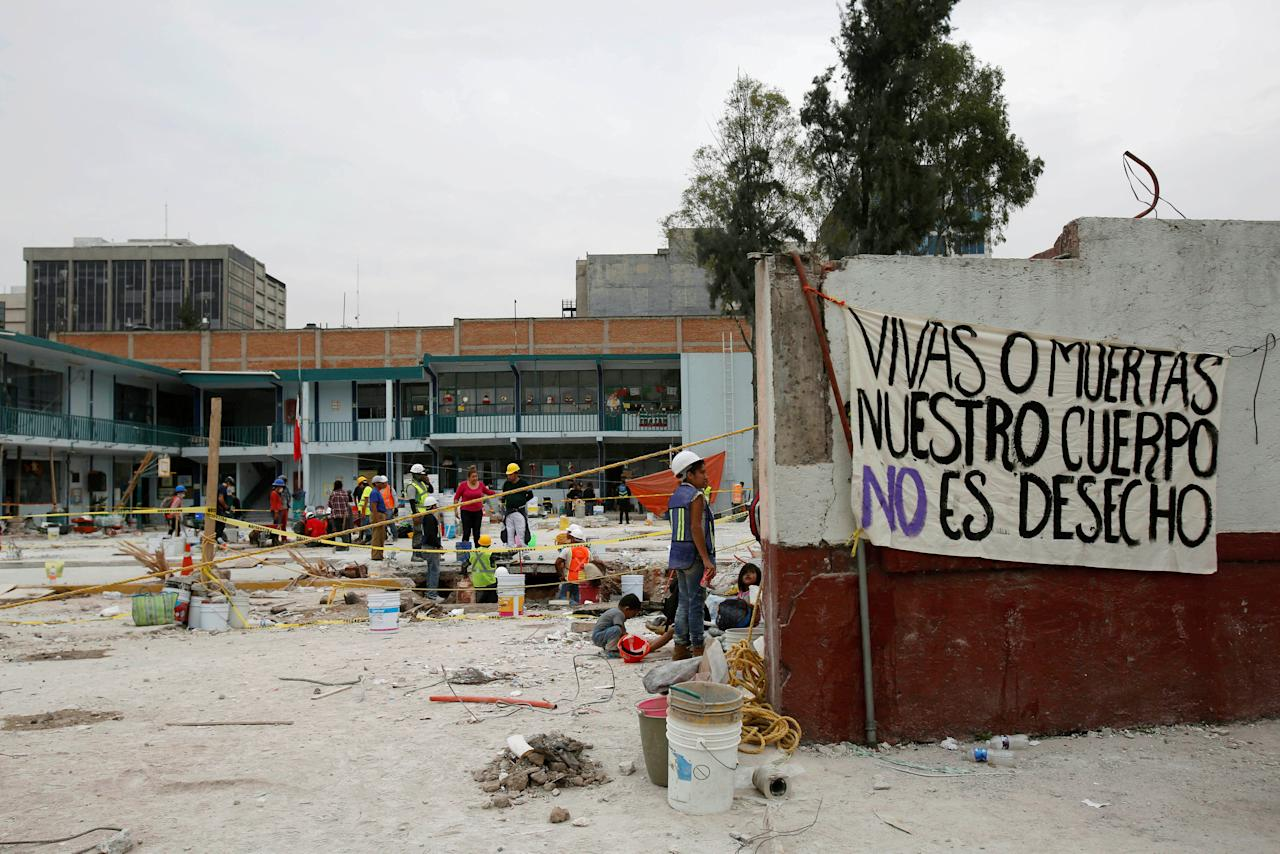 "A sign reading ""Alive or dead, our bodies are not scrap,"" is pictured as volunteers work at a site where a factory building collapsed in an earthquake, killing several people, in Mexico City, Mexico September 23, 2017.  REUTERS/Ginnette Riquelme"