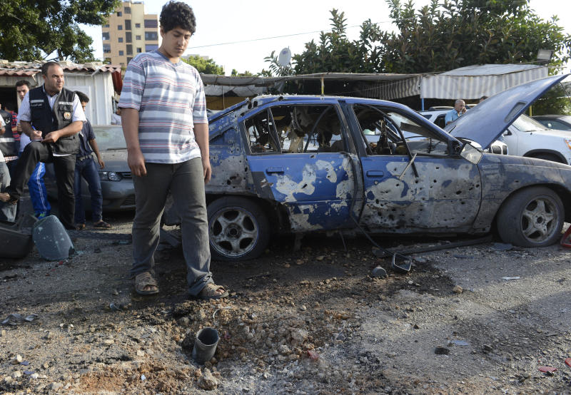 A Lebanese man looks at a part of a rocket, seen on the ground, which struck a car exhibit, near a damaged car at the Mar Mikhael district south of Beirut, Lebanon, Sunday May 26, 2013. Rockets slammed Sunday into two Beirut neighborhoods that are strongholds of Lebanon's Hezbollah group, wounding at least 4 people, Lebanese security officials and media said. Tensions have been running high in Lebanon, and Syrian rebels have threatened to retaliate against the militant Shiite Hezbollah group for sending fighters to assist President Bashar Assad's forces in Syria. (AP Photo/Ahmad Omar)