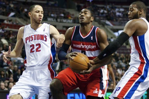 Washington Wizards' John Wall, center, drives between Detroit Pistons' Tayshaun Prince (22) and Greg Monroe, right, in the first half of an NBA basketball game, Sunday, Feb. 12, 2012, in Auburn Hills, Mich. (AP Photo/Duane Burleson)