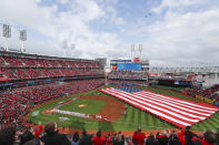 Spectators stand for the national anthem before an opening day baseball game between the Cincinnati Reds and the Washington Nationals, Friday, March 30, 2018, in Cincinnati. (AP Photo/John Minchillo)