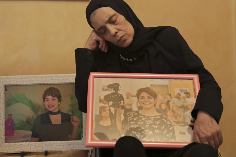 """In this Nov. 17, 2019 photo, Majida holds a photo of her daughter Nadyn Jouny as she attends a 40 day mourning ceremony of her death in a car accident, at their family house in southern Beirut, Lebanon. In death as in life, Jouny -- affectionately called Om Karam, Arabic for """"mother of Karam"""" -- has showcased the struggles of Lebanese women who are battling laws that give religious courts say over many aspects of their lives. (AP Photo/Hassan Ammar)"""