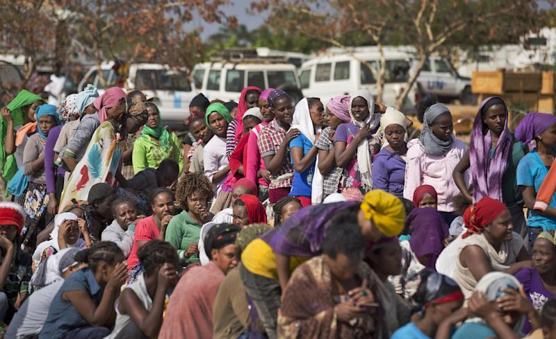 Displaced women, including foreigners, queue inside the United Nations camp where they have sought shelter in Malakal, South Sudan, Monday, Dec. 30, 2013. When violence broke out in Juba on Dec. 15 life remained calm but tense in Malakal, the capital of oil-producing Upper Nile state, but the violence then radiated outward from Juba and full-fledged war broke out in the town on Christmas Day, as army commanders defected and pledged allegiance to the country's ousted vice president, in most cases pitting the ethnic group of President Salva Kiir, a Dinka, against ethnic Nuers. (AP Photo/Ben Curtis)