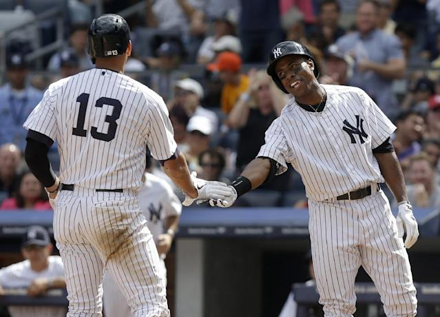 New York Yankees' Alex Rodriguez, left, is greeted by temmate Curtis Granderson after scoring on a double hit by Mark Reynolds during the fourth inning of the baseball game against the Boston Red Sox at Yankee Stadium, Sunday, Sept. 8, 2013, in New York. (AP Photo/Seth Wenig)