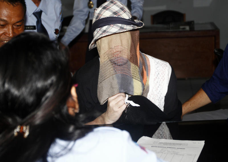 Australian Schapelle Corby, covering her face, listens to an official after she received her parole in Bali, Indonesia, Monday, Feb. 10, 2014. The Australian woman convicted of smuggling marijuana into Indonesia in 2005 has been released from jail on parole. She was convicted of smuggling 4.2 kilograms (9 pounds) of marijuana onto Bali and sentenced to 20 years in prison. (AP Photo/Firdia Lisnawati)