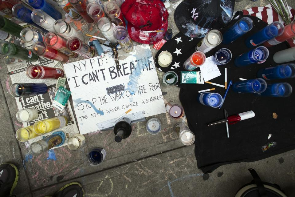FILE - In this Saturday, July 19, 2014, file photo, a memorial for Eric Garner rests on the pavement near the site of his death, in the Staten Island borough of New York. In 2014, the world witnessed a New York police officer put Garner in a chokehold while arresting him for allegedly selling illegal cigarettes in Staten Island. The video, which would go on to set precedence for the documentation of police brutality, highlighted the use of a chokehold by the police department, which had banned the method in November 1993. But unlike in the aftermath of George Floyd's killing in 2020, little to no legislative change was spurred from Garner's death. (AP Photo/John Minchillo, File)