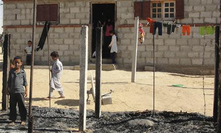 Boys look at a burnt area around a house after assaults on militant targets by the Egyptian Army, in a village on the outskirts of Sheikh Zuweid, near the city of El-Arish in Egypt's Sinai peninsula in this September 10, 2013 file photo. REUTERS/Stringer /Files