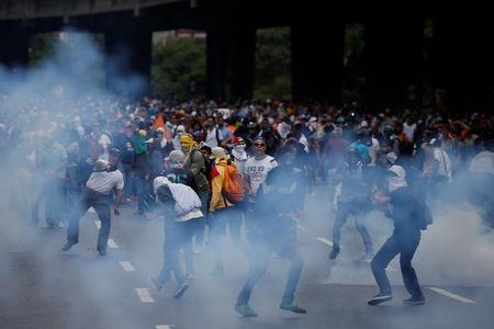 Demonstrators are seen amidst tear gas fired by security forces during an opposition rally in Caracas