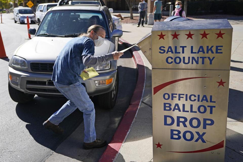 Chris Tapscott inserts his ballot in a ballot drop box Tuesday, Oct. 20, 2020, in Salt Lake City. (AP Photo/Rick Bowmer)