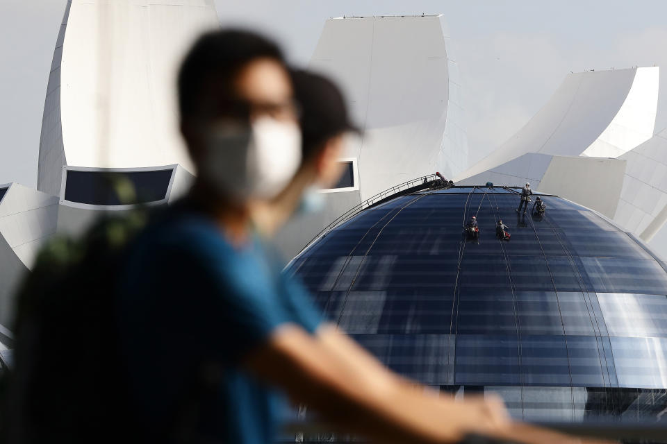 Workers perform maintenance work on the dome of the Apple store at Marina Bay Sands in Singapore.