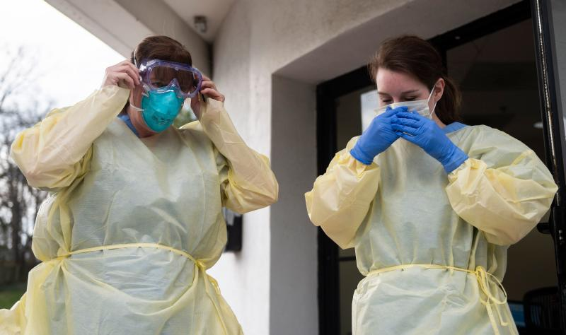 Health care workers from Virginia Hospital Center put on their personal protective equipment before people arrive at a drive through testing site for coronavirus in Arlington, Virginia. on March 20, 2020. (Photo by ANDREW CABALLERO-REYNOLDS / AFP) (Photo by ANDREW CABALLERO-REYNOLDS/AFP via Getty Images)