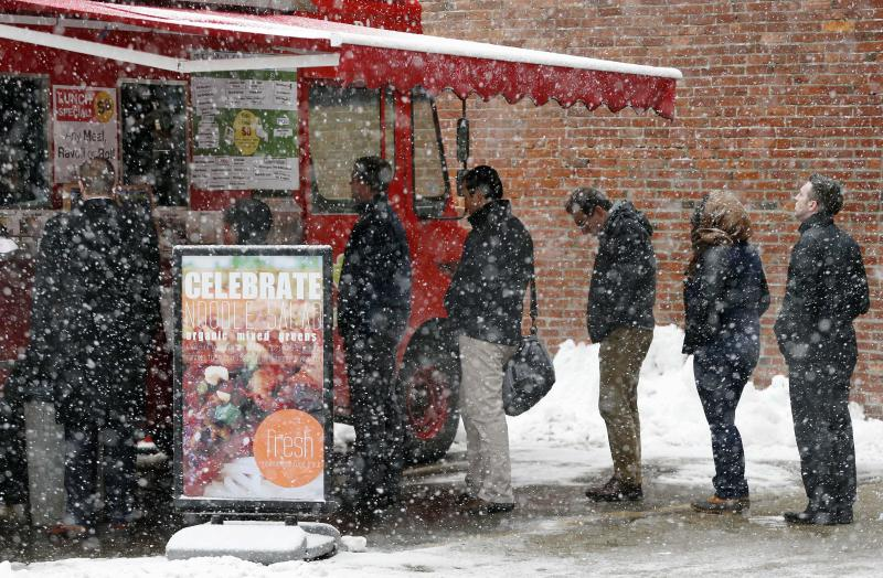 People wait in line at a food truck in Boston as snow from the latest storm to hit the area begins to fall, Tuesday, Feb. 18, 2014. (AP Photo/Michael Dwyer)