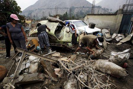 People remove debris of cars and houses after a massive landslide in Chosica, March 24, 2015. REUTERS/Mariana Bazo