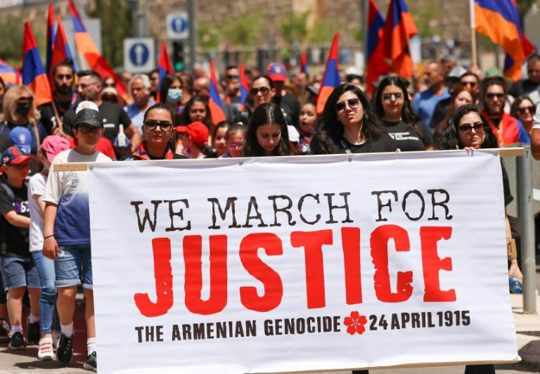 Armenians carry national flags and a large banner during a march in Jerusalem to commemorate the anniversary of mass killings by Ottoman Turkey