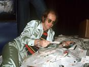<p>Elton John poses in a silky green tracksuit with a striped tee on a mountainous pile of fan mail in 1976. (Photo: Getty Images) </p>