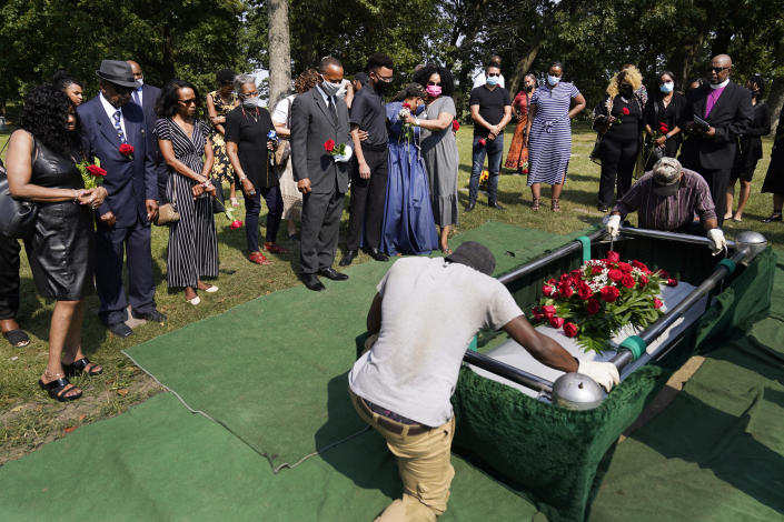 Friends and family of Hosea Knox watch as his casket is lowered into a plot next to his wife, Bobby, Monday, Sept. 13, 2021, at the Mount Hope Cemetery on the South Side of Chicago. (AP Photo/Charles Rex Arbogast)