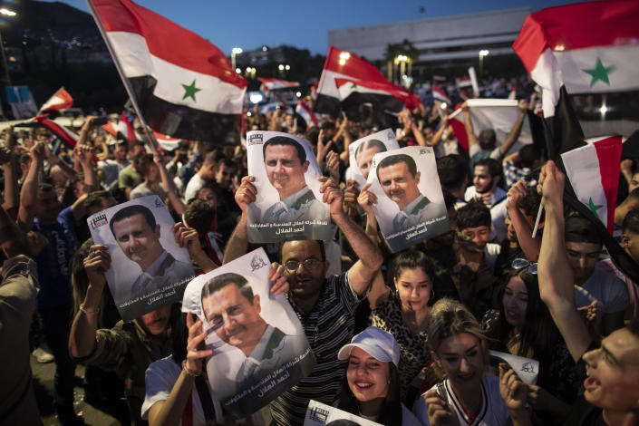 Syrian President Bashar Assad supporters hold up national flags and pictures of Assad as they celebrate at Omayyad Square, in Damascus, Syria, Thursday, May 27, 2021. (AP Photo/Hassan Ammar)