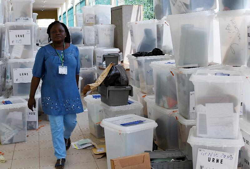 An official from Ivory Coast's Independent Electoral Commission (IEC) walks past ballot boxes as the commission checks the results at a polling station in Abidjan on October 26, 2015 (AFP Photo/Sia Kambou)