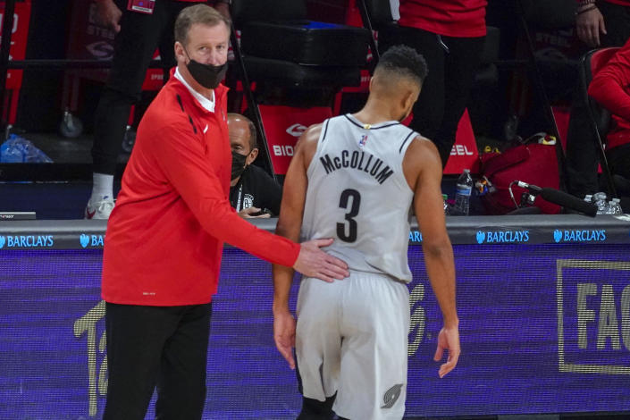 Portland Trail Blazers coach Terry Stotts pats guard CJ McCollum (3), who heads to the bench during the first half of the team's NBA basketball game against the Brooklyn Nets, Friday, April 30, 2021, in New York. (AP Photo/Mary Altaffer)