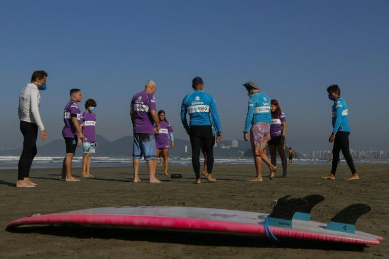 Brazilian surfers Miguel Almeida and Malu Mendes pray before training in the Adapted Surf School at Gonzaga Beach, in Santos, Sao Paulo, Brazil on June 2, 2021