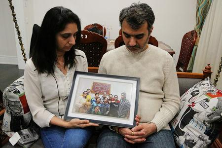 Manant and Hiral Vaidya (at left in the picture) hold a photograph showing six members of their family who were among the 157 people who perished when Ethiopian Airlines Flight ET 302 crashed on Sunday, at their home in the Toronto suburb of Brampton, Ontario, Canada, March 13, 2019. REUTERS/Chris Helgren