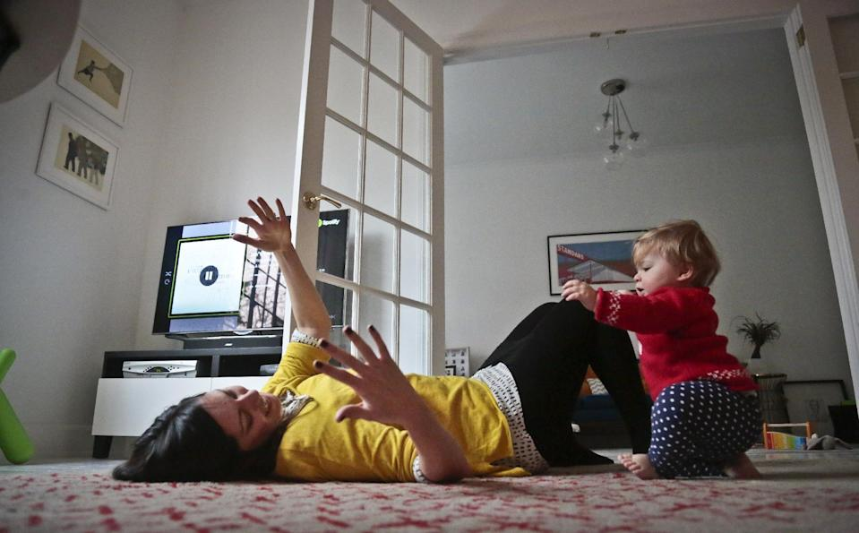 """In this Nov. 26, 2013 photo, Shirin Majid plays with her daughter, Ella Townsend, 9 months, at their home in New York. Majid, who works for the Internet startup Quirky, is home during her company's quarterly """"blackout"""" week break from work. Quirky's CEO, Ben Kaufman, makes the whole company stop working and take breaks so they don't burn out. (AP Photo/Bebeto Matthews)"""