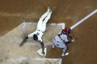 Milwaukee Brewers' Lorenzo Cain scores past St. Louis Cardinals catcher Yadier Molina during the sixth inning of a baseball game Wednesday, May 12, 2021, in Milwaukee. Cain scored from second on a ball hit by Travis Shaw. (AP Photo/Morry Gash)