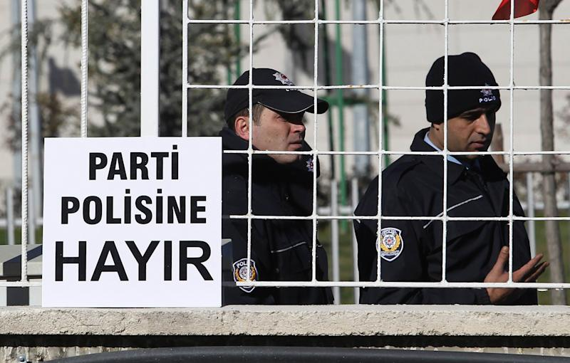 Turkish police look on as family members of security officers who were fired after they conducted a corruption investigation demonstrate outside the Constitutional Court in Ankara on December 24, 2014 (AFP Photo/Adem Altan)