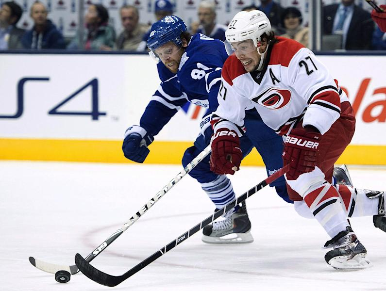 Toronto Maple Leafs forward Phil Kessel, back, chases down Carolina Hurricanes defenceman Justin Faulk during the second period of an NHL hockey game in Toronto on Thursday, Oct. 17, 2013. (AP Photo/The Canadian Press, Nathan Denette)