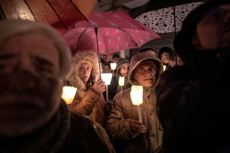 People hold torches and candles during a demonstration against anti-Semitism in Mondovi, northwestern Italy