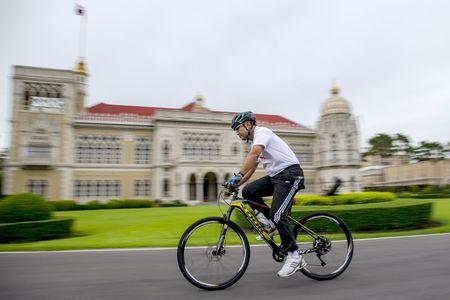 Thailand's Prime Minister Prayuth Chan-ocha rides a bicycle before a cabinet meeting at Government house in Bangkok, Thailand, September 15, 2015. REUTERS/Athit Perawongmetha
