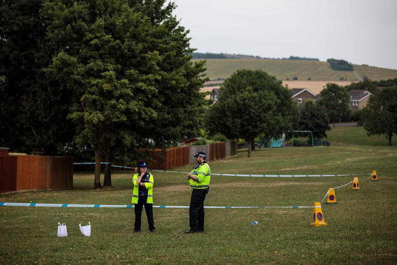 Police officers stand at a cordon around an area of grass after two people in their 40s were poisoned in the UK. Source Getty ImagesMore